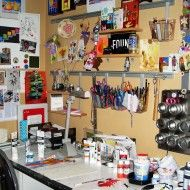 """Jill Helms: """"Lots of tiny pieces of aluminum cans are scattered about my studio when I'm creating Recycled Metal Mosaics. Boxes of recycled cans, organized by color, fill the bottom shelves. The middle shelves store paints, paper, canvas, brushes & inspiring photos. The top shelves hold my jewelry supplies. Photos of friends, favorite quotes, inspiring images, & tools of all kinds are mounted on the wall in front of my desk. This is my creative space where I go to be in the art zone."""""""