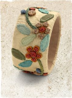 April Flowers Bangle - Wrapped in vanilla silk, wide bangle is embellished with a garland of colorful appliqué leaves and beaded daisies. Made in Peru, shown on the Peruvian Connection.