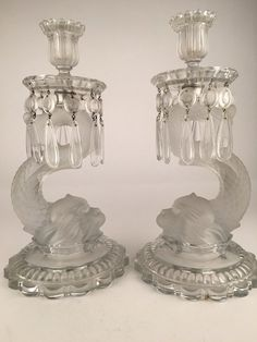 Baccarat pair of Dolphin candlesticks in clear and frosted glass. Each candlestick with a molded Baccarat signature and each with 10 hanging prisms. Overall height 13 inches.