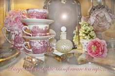 A perfect English Boudoir with red transferware tea cups, pink roses and silver under a soft glow . . .