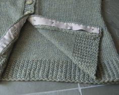 Great tip!!   Knit cardigans especially tend to pull and gape) so add some grosgrain ribbon to the back of the button band to hopefully help with that.