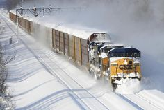 A CSX freight train plows its way past the Cemetery Rd. overpass in Lancaster, N.Y. Wednesday, Nov. 19, 2014. A lake-effect snow storm dumped over five feet of snow in areas across Western New York. Another two to three feet of snow is expected in the area, bringing snow totals to over 100 inches, almost a years' worth of snow in three days.