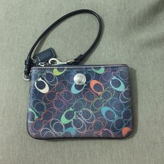 Coach Wristlet multi color Small Coach Wristlet, a few years old. Has a light stain inside but outside is in great condition. Yes authentic. Coach Bags Clutches & Wristlets