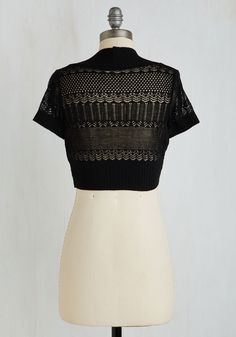 Take in the sights of a Gatsbian city adorned in this daring black shrug. Flaunting a delicate, scalloped and geometric lace pattern, short sleeves, and a ribbed hem, this ebony cardigan will leave you shining even in the wake of the Chrysler Building.