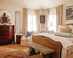 This master bedroom is a retreat, with a club chair for reading. The torso on the dresser does double duty as a display for necklaces.