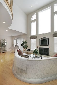 2-story ceiling with landing look down on this all-white living room with semi-circular sofa facing the fireplace and TV.  Piano off to one side.