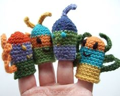 our crocheted finger puppets displayed on a hand. Puppets have embroidered features and wiggly crocheted antennae and legs.