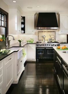 Perfect kitchen. Dark wood flooring, white/cream units and black appliances