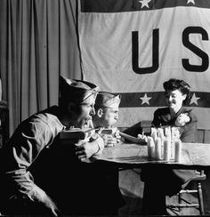 """Soldiers compete at candle bowling in Waynesville, Mo. Men blowing out candles while a woman keeps score (the scores are scored like a bowling game) at the USO. Location: Waynesville, MO; Date taken: 1942; Photographer: John Phillips. Featured in LIFE magazine June 29, 1942 article, """"USO In Peace and War It Has Proven Its Worth"""". 