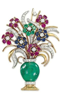 A MULTI-GEM AND DIAMOND BROOCH - Modelled as a bouquet of flowers, the emerald bead vase with circular-cut diamond base and collar, to the ruby, sapphire and emerald cluster flower spray above, with further diamond-set leaves and buds, circa 1950