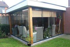 Gumax glazen schuifdeuren in een houten terrasoverkapping met deurgrepen en tochtstrips. #glazenschuifwanden
