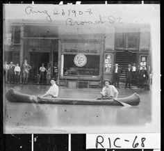 Aug. 26, 1908.; Canoeing down Broad Street during the flood. In the background is the Atlantic Coast Line Railway Company