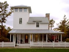 A white picket fence stands guard at the front of this contemporary farmhouse. Complete with a tin roof, stone chimney and inviting front porch, the home is a picture of country charm. The third-story tower offers an unexpected twist in typical farmhouse design.