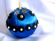 Vintage satin Christmas ornament, this blue ball has been decorated with black flower trim held in place with a large white-headed pins.