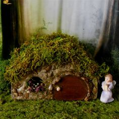 Welcome and thank you for visiting my shop. It brings me great solace when Im making my fairy garden items or puttering in my miniature garden. It is my sincere wish my work brings you some comfort and joy too!  This cozy little stone fairy house is sure to attract the wee folk to your garden! A round door and window filled with cheerful flowers give this house a hobbit home feel. Made of durable concrete and stone to last for years to come, ready for outdoor use. The house is 6 inches wide…