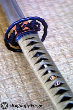 Tsuka wrapped in olive silk ito over black lacquered same. Menuki of silver and gold ken. Tsuba of antique wrought iron in the Higo style with shore pine motif. By Michael Bell. #dragonflyforge #sword #katana #japanessword #martialarts #swordsmith #bladesmith #forge #art #handcrafted #luxurygiftsformen #giftsformen #uniquegifts