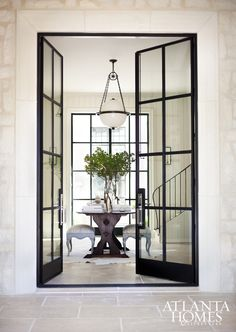 A pair of iron-and-glass doors by RG Ironworks fashion a grand entrance into the foyer, where an industrial pendant from Circa Lighting hangs above an entry table.