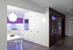 Dominantná nábytková stena, ktorá vychádza z presne definovanej požiadavky na rozsah a formu úložných priestorov, sa tiahne celým otvoreným priestorom od spálne až po koniec kuchyne.