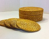 """4 piece round wicker coaster set with wicker coaster holder. would look lovely on a side table. There is a small red spot on one of the coasters and and a few small spots where wicker has lifted just a little bit.  Measurements are 3 3/4"""" on the coasters and 5"""" wide x 2 1/2"""" tall."""