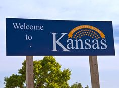 "Kansas's signs are a mishmash of its state seal (emblazoned with the Latin phrase ""Ad Astra per Aspera,"" translating to ""To the Stars Through Difficulties"") and the state flag, which features a sunflower, the official state flower."