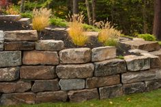 Stone retaining wall next to outdoor patio and rear ground-level basement entrance. Custom green homes in Saratoga Springs, NY by Capital Construction.