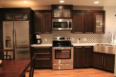Expresso cabinets, light wood floors.  Cambria quartz countertops in Whitney.