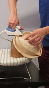 someone creating folds in a straw hat with an iron.
