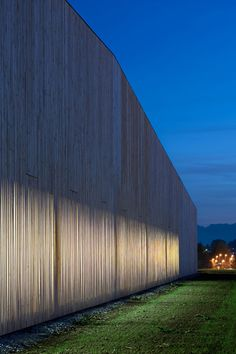 Toothpick-shaped gaps allow light into timber-clad sports centre.