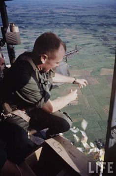 Dropping propaganda leaflets out of a Huey on a Delta Patrol 1967 - Photo by Larry Burrows ~ Vietnam War