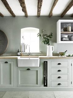 White farmhouse sink with muted green cabinets via Neptune