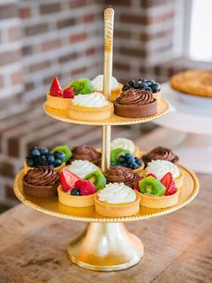 Stack an assortment of fruit tarts and mousse on elegant tiered plates for southern wedding sophistication.