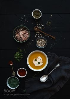 Pumpkin soup with cream seedsand various spicesl in rustic metal bowl over grunge black background. by 2enroute