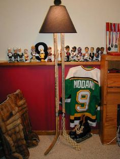 Three hockey sticks. Pucks for spacers. Lamp kit: http://www.homedepot.com/p/Westinghouse-3-Way-Socket-Make-A-Lamp-Kit-7026800/100351517#.UZZgD-DTLFJ