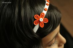 A plain white hair band decorated by quilling