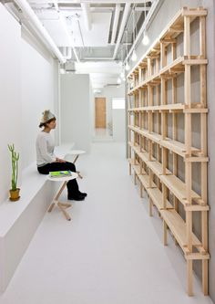 A timber lattice supports shelves, worktops, lighting and mirrors down one side of this beauty salon in Osaka