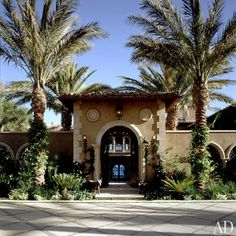 """""""The entire project was a collaboration between Cher and me,"""" says Wilson. """"She was totally involved with the landscape design—which is unbelievable. She's very gifted."""" Seen here is the gated entrance, and a spacious courtyard beyond, from the private driveway."""