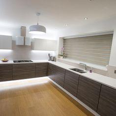 Handleless walnut effect kitchen with white quartz work surfaces nestkitchens.co.uk