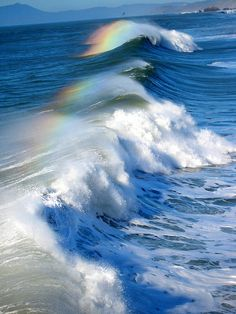 Prisms of light create rainbows on ocean waves.