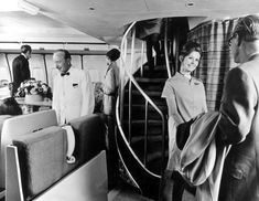 British Overseas Airways Corporation (BOAC) air hostess greets a passenger in front of a spiral staircase aboard a Boeing 747 Monarch jet, Jan. 15, 1970. (Getty Images)