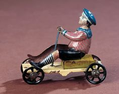 """German Tin Mechanical Penny Toy,""""Boy on Cart"""" by Meier - Theriault's Antique Doll Auctions"""