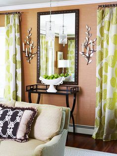 Lighten Up. For an easy splash of color, outfit windows in treatments with bold hues and unique patterns. Here, unlikely leafy curtains transform this muted space into a fabulously lively living room. Place a few accessories mimicking the color scheme around the room, such as the cute bowl of apples shown here. Glimmering candle sconces on either side of the mirror tie the natural theme together.