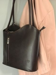 From work to weekend - we love this backpack purse. This versatile handbag has a simple sleek design that is perfect for business and converts to a backpack for more casual weekend wear. This Dark Brown is stunning - available in many colors. #backpackbags #businesscasualoutfits #businesscasualoutfitsforwomen #businesscasualoutfitsyoungprofessional #pursesandhandbags #italianleatherbag #italianleatherhandbags #backpackstyle #totehandbags #fashionstyle Italian Leather Handbags, Leather Purses, Leather Bag, Backpack Purse, Fashion Backpack, Tote Handbags, Purses And Handbags, Business Casual Outfits For Women, Casual Weekend
