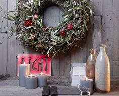 The wreath is cool, but I'm attracted to sign behind the candles. Could make for some very cool and different holiday decorations.
