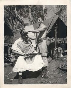"""Marine """"barber"""" uses a Japanese flag as an apron on Cape Gloucester. Note that the """"client"""" keeps his rifle handy. Barber Shop Chairs, Barber Shop Decor, Barber Chair, Mobile Barber, Barber Clippers, Beard Logo, Wet Shaving, Vintage Hairstyles, Hair Cuts"""