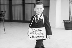 "Ring bearer holding a ""Daddy here comes mommy"" sign 