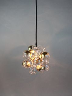 Eighteen hand blown glass bubbles float around a center light globe, diffusing the light into a natural glow. The most compact of our custom