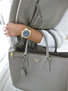 Understated chic, despite the man's gold watch: with a heavy white pullover, a grey scarf + Prada bag.