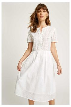 This white dress is made from airy organic cotton that's woven with a floral broderie anglaise pattern. It's pleated for subtle volume and beautifully appliquéd along the hem.
