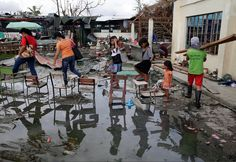 Villagers cross over a muddy road by stepping on school chairs in an area destroyed by Typhoon Haiyan in Tacloban, central Philippines, on November 26, 2013. Photo: Bullit Marquez / AP