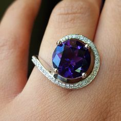 Arizona Amethyst Gold JewelryRound Swirl Ring. This ring features a stunning round Arizona Amethyst, weighing about 5 carats, and measuring 11.5 mm! Surrounding this statement-making stone is a swirl of Diamonds in graduated sizes, weighing .30 carats in total. •$3,995.00